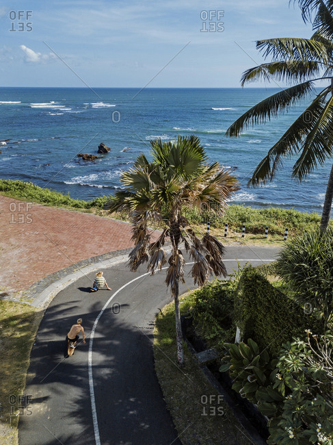 Indonesia-Bali-Twoyoung men skateboarding along coastal road with sea in background