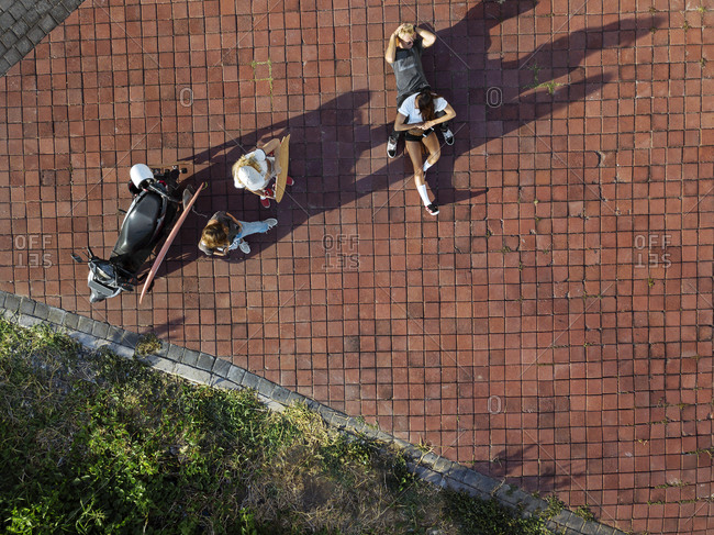Indonesia- Bali- Aerial view of group of friends hanging around cobblestoned area