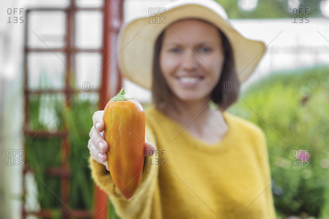 Smiling woman holding orange bell pepper while standing at greenhouse
