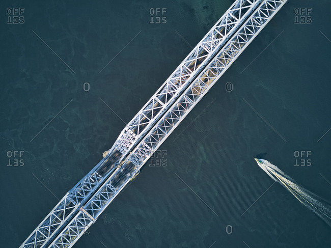 Directly above aerial view of boat moving over Volga River under metallic railway bridge
