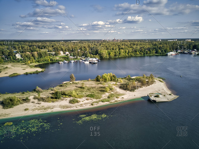 Scenic view of Volga River with algae and boats against sky on sunny day