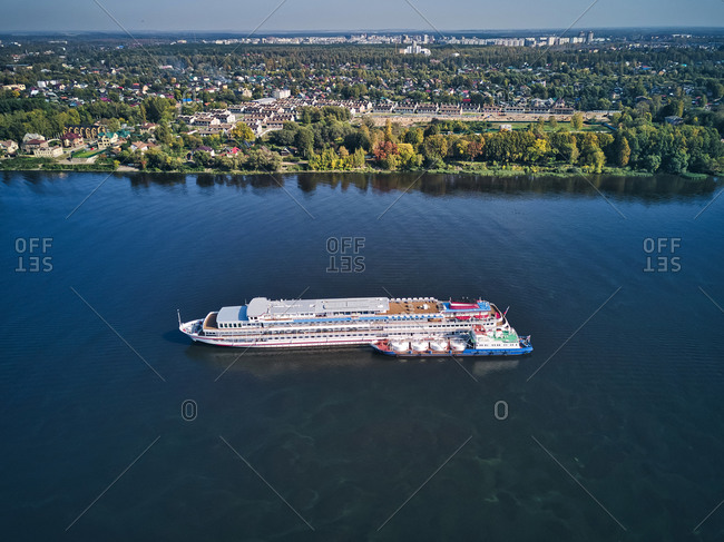Aerial view of recreational boat being refueled from barge on Volga River near city