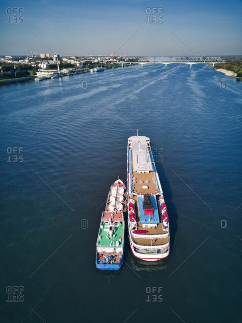 Barge refueling recreational boat on Volga River against sky