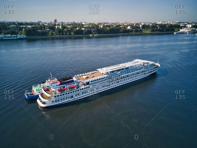 Aerial view of recreational boat being refueled from barge on Volga River near city during sunny day