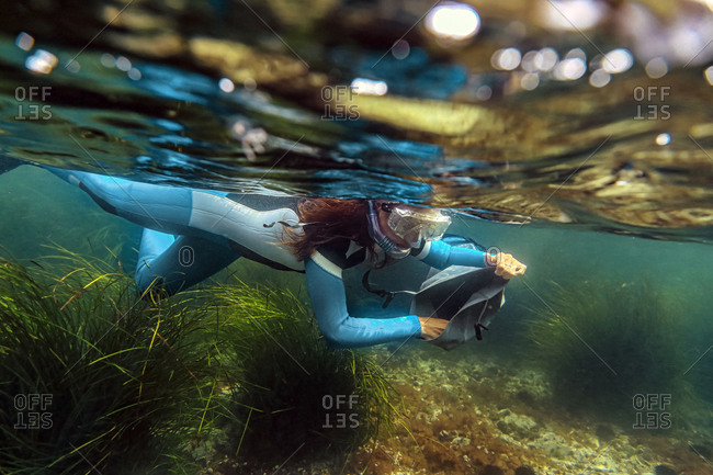 Mid adult woman collecting seafood in bag while diving into sea