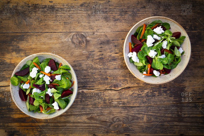 Two bowls of vegetarian salad with roasted carrot strips- beetroot- corn salad- goat cheese and Spanish onions