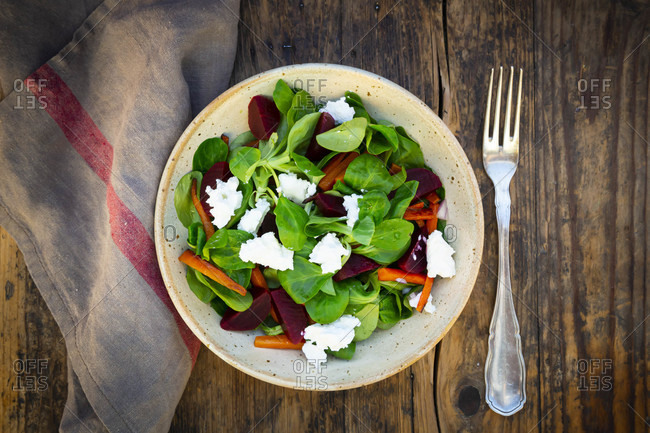 Bowl of vegetarian salad with roasted carrot strips- beetroot- corn salad- goat cheese and Spanish onions