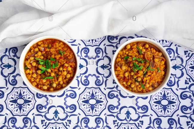Two bowls of vegan stew with chick-peas- red lentils- tomatoes- Spanish onions and mint
