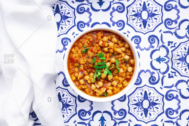 Bowl of vegan stew with chick-peas- red lentils- tomatoes- Spanish onions and mint
