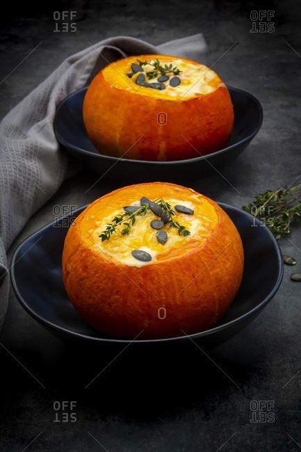 Studio shot of two Hokkaido pumpkins stuffed withcamembertcheese- thyme and pumpkin seeds