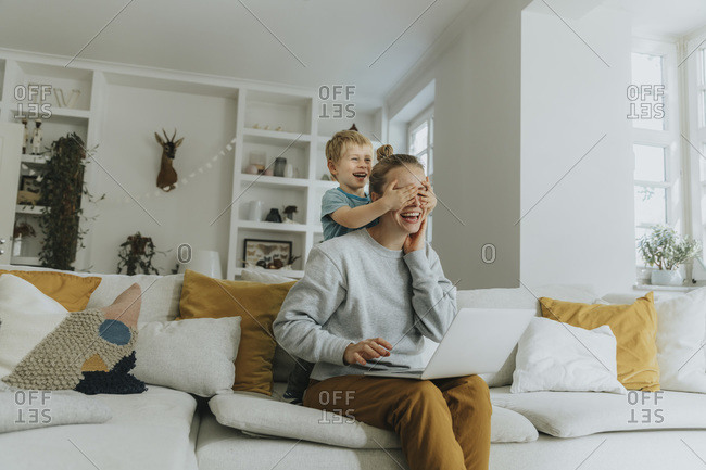 Smiling boy covering mother eyes while standing on sofa at home