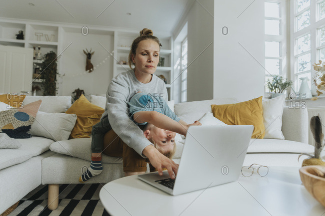 Mother taking care of boy while working on laptop at home