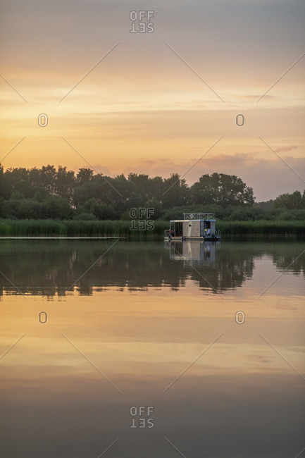 Reflecting image of houseboat in lake during sunset