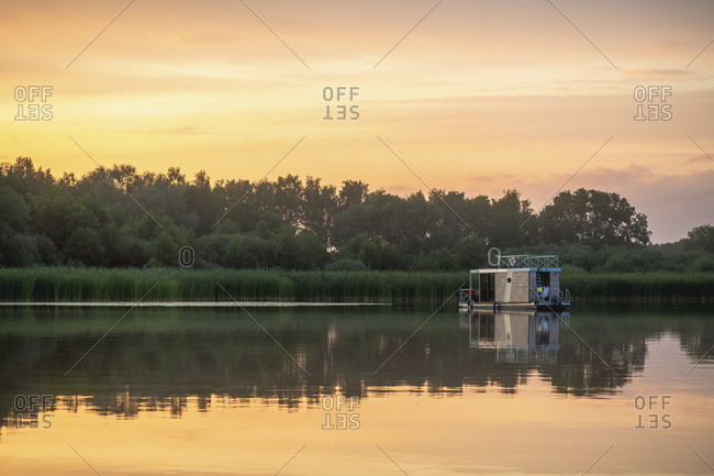 Reflection of houseboat in lake during sunset