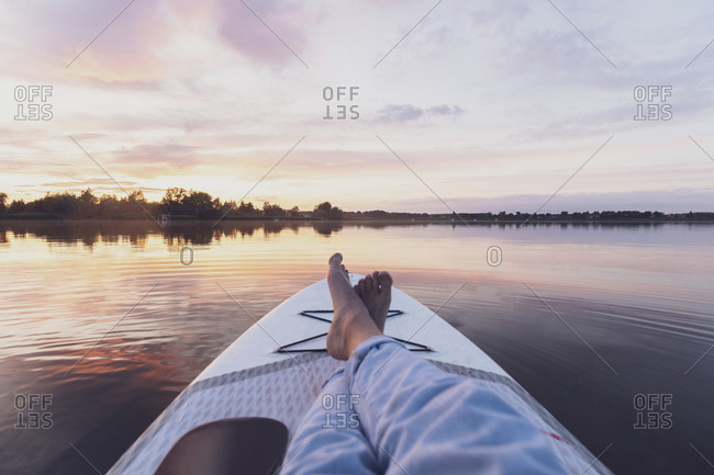 Legs of woman relaxing on paddleboard during sunset