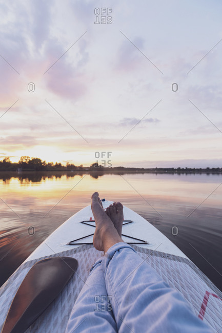 Legs of woman resting on paddleboard during sunset
