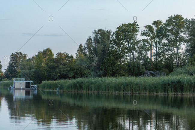 Scenic view of nature and houseboat in lake during sunset