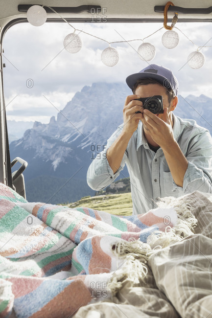 Male tourist photographing interior of campervan against mountains- Sesto Dolomites- Dolomites- Alto Adige- Italy