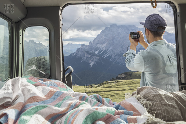 Man photographing scenic mountain ranges while standing by campervan. Sesto Dolomites- Dolomites- Alto Adige- Italy