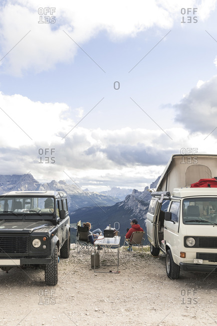 Male and female tourists enjoying vacation while sitting by vehicles at Sesto Dolomites- Dolomites- Alto Adige- Italy