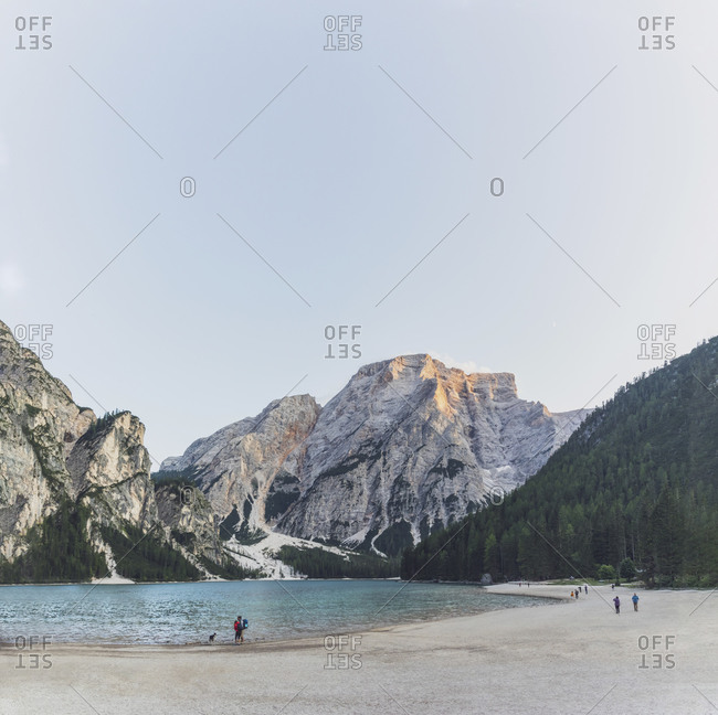 People at Pragser Wildsee near snowcapped mountain against clear sky- Dolomites- Alto Adige- Italy