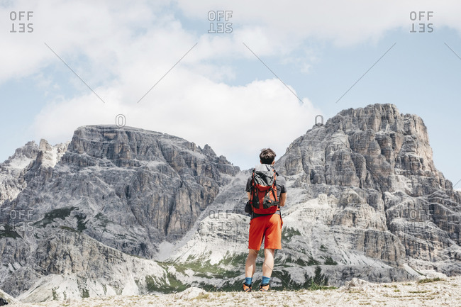 Male tourist looking at famous Tre Cime di Lavaredo against sky- Sesto Dolomites- Dolomites- Alto Adige- Italy