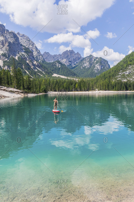 Man paddleboarding on turquoise Pragser Wildsee against mountain range- Dolomites- Alto Adige- Italy