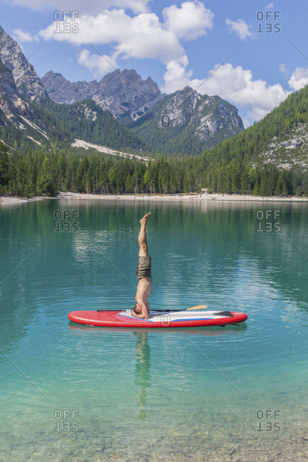 Man doing headstand on paddleboard at Pragser Wildsee against mountain range- Dolomites- Alto Adige- Italy