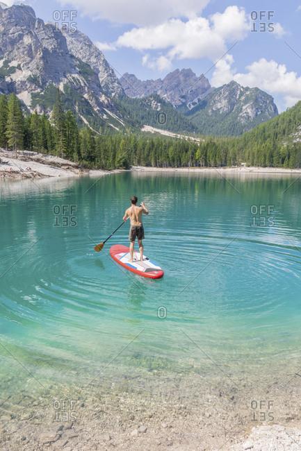 Man paddleboarding on turquoise Pragser Wildsee- Dolomites- Alto Adige- Italy