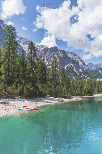 Paddleboards at Pragser Wildsee lakeshore by trees on sunny day- Dolomites- Alto Adige- Italy