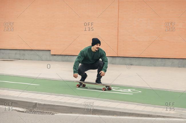 Young man skateboarding along bicycle lane
