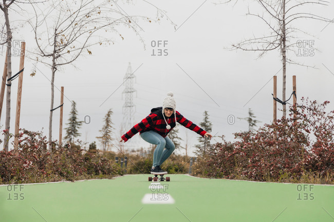 Young woman skateboarding outdoors in the winter