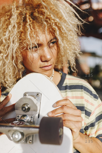 Hispanic woman with blond curly hair looking away while holding skateboard on sunny day