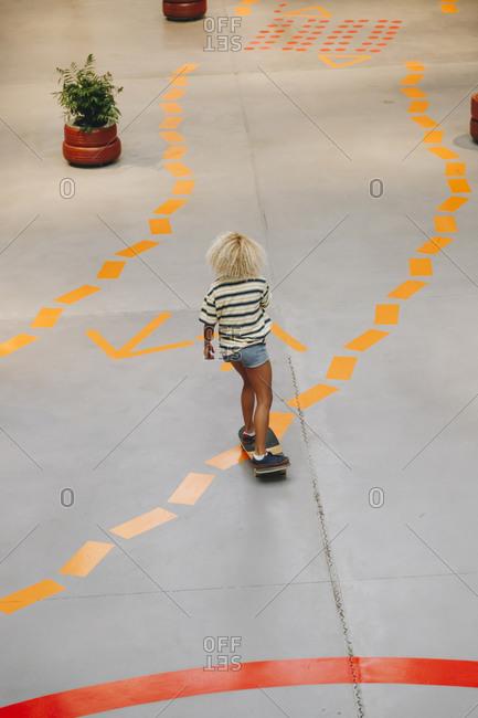 Blond woman skateboarding on footpath with orange road marking