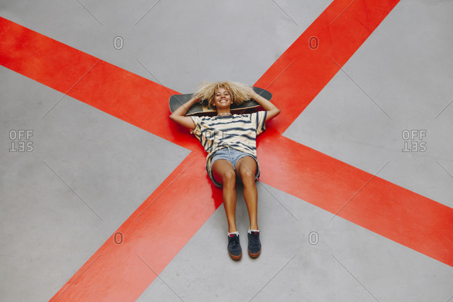 Smiling blond Afro woman lying with skateboard on orange road marking