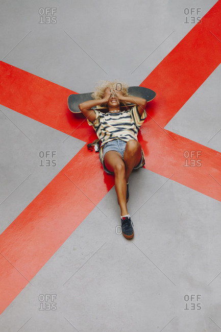 Blond Afro woman lying with head in hands on orange road marking