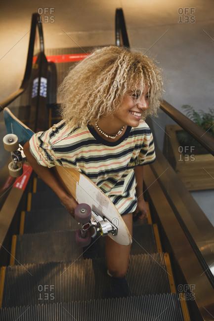 Smiling blond Hispanic woman holding skateboard while standing on escalator