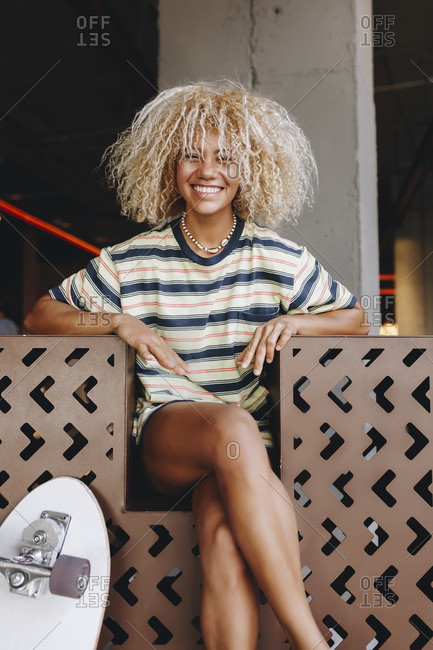 Cheerful blond Afro woman sitting with legs crossed