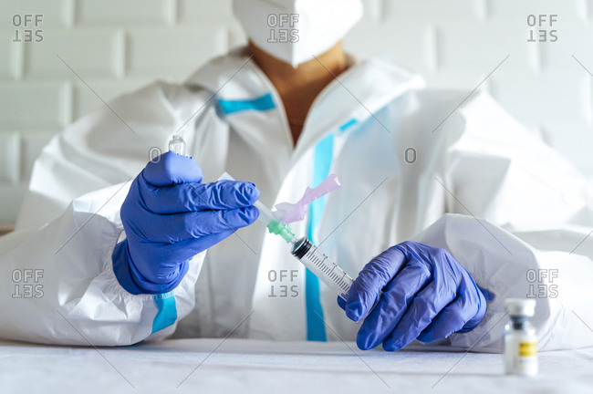 Nurse in protective workwear filling injection while sitting by table in hospital