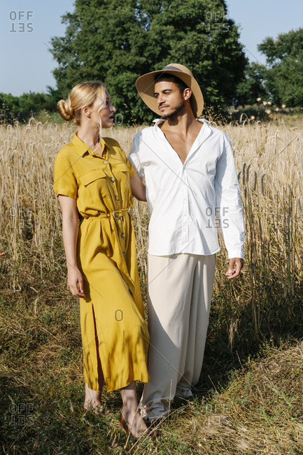 Young couple looking at each other while standing on meadow during sunny day