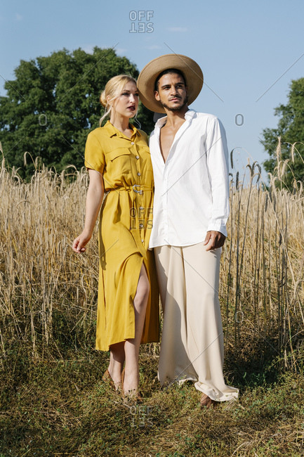 Multi-ethnic couple looking away standing together at meadow on sunny day
