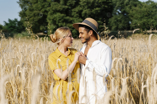 Smiling couple holding hands while looking at each other standing amidst crops on sunny day
