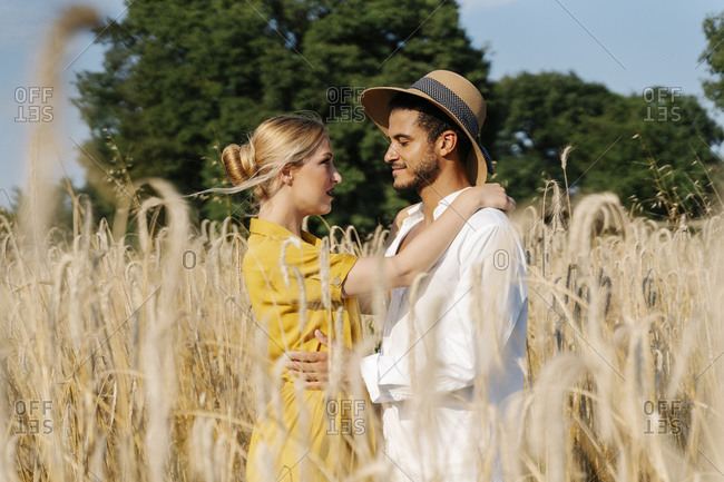 Romantic couple looking at each other while standing on field during sunny day