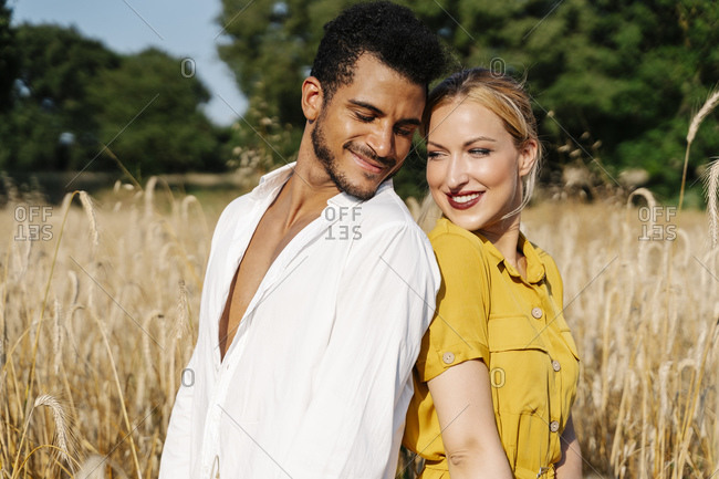 Smiling man and woman looking at each other while standing back to back on meadow