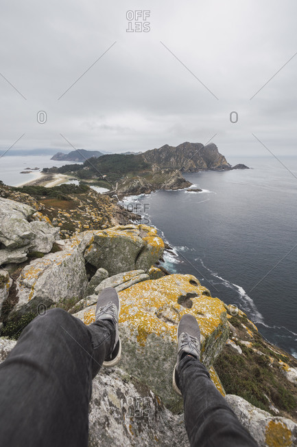 Low section of young male tourist over rock formation against cloudy sky- Cies Islands- Vigo- Pontevedra Province- Galicia- Spain