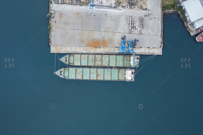 Drone view of container ships moored by dock at port on blue sea