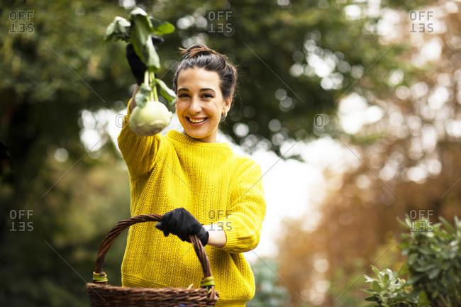Woman showing kohlrabi while standing at urban garden