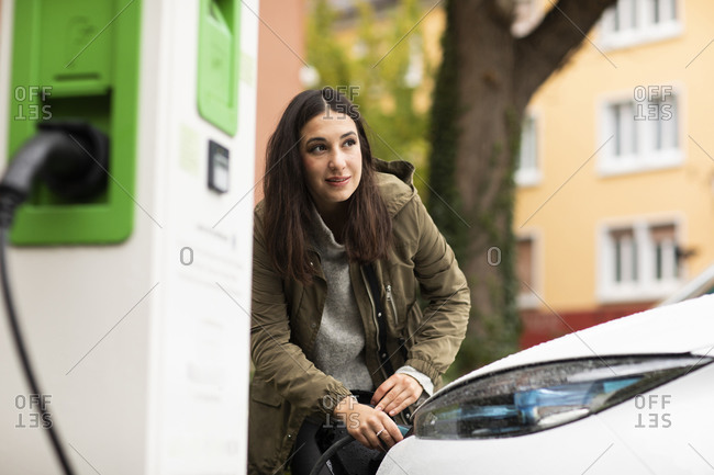 Beautiful woman removing electric plug from car at charging station