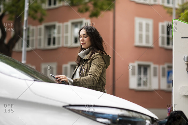 Confident beautiful woman using smart phone for renting electric car at charging station