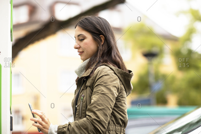 Beautiful woman using smart phone for renting electric car at charging station